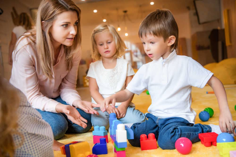 Mother playing with child to promote learning through play before starting kindergarten/ promote kindergarten readiness