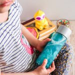 child playing with sensory bottle in calm down corner