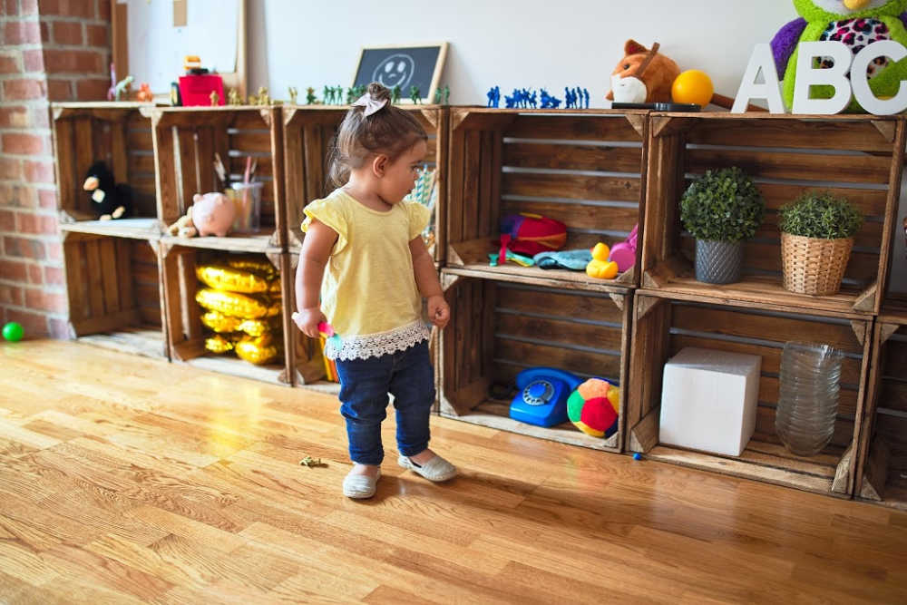 Toddler in an organized, minimalistic playroom.
