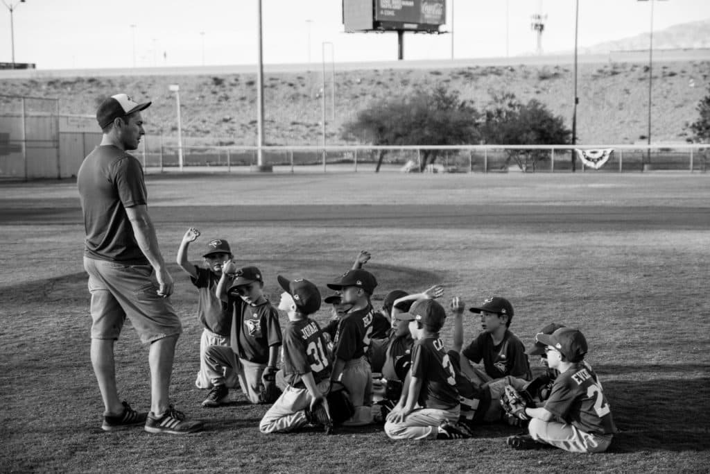 When summer hits, naturally parents want to avoid the summer slide. We want to schedule enough summer activities so that our children are challenged and go back to school ready. While all of this is done with the best of intentions, free play is more beneficial than most of these extracurricular activities for kids. This is why. Photo of kids listening to baseball coach. Photo credit unsplash photography.