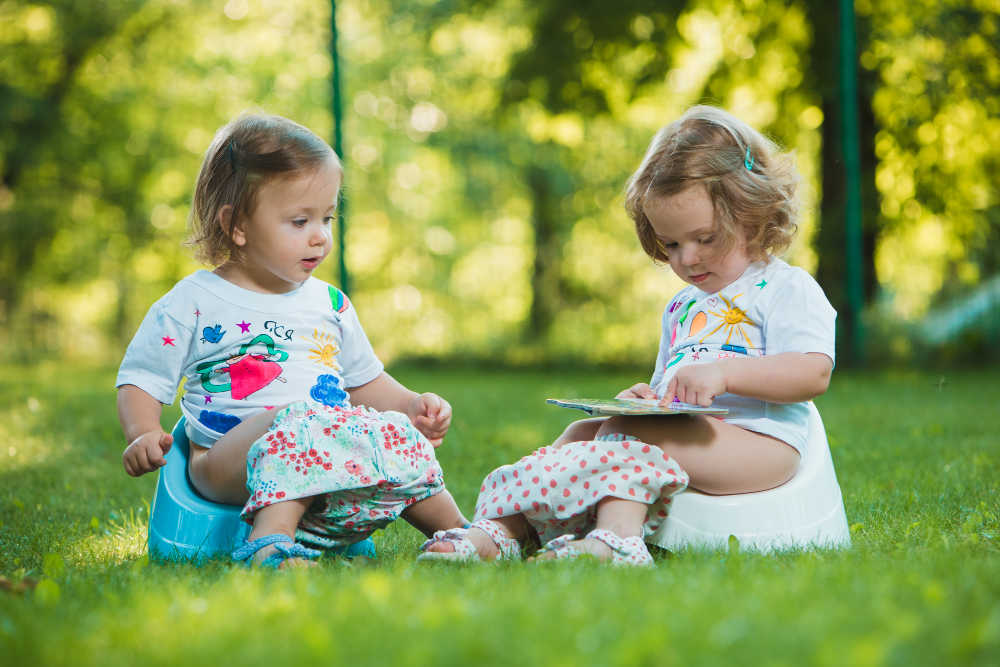 toddler girls read books on the potty