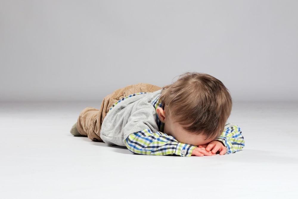 sad toddler boy crying on floor