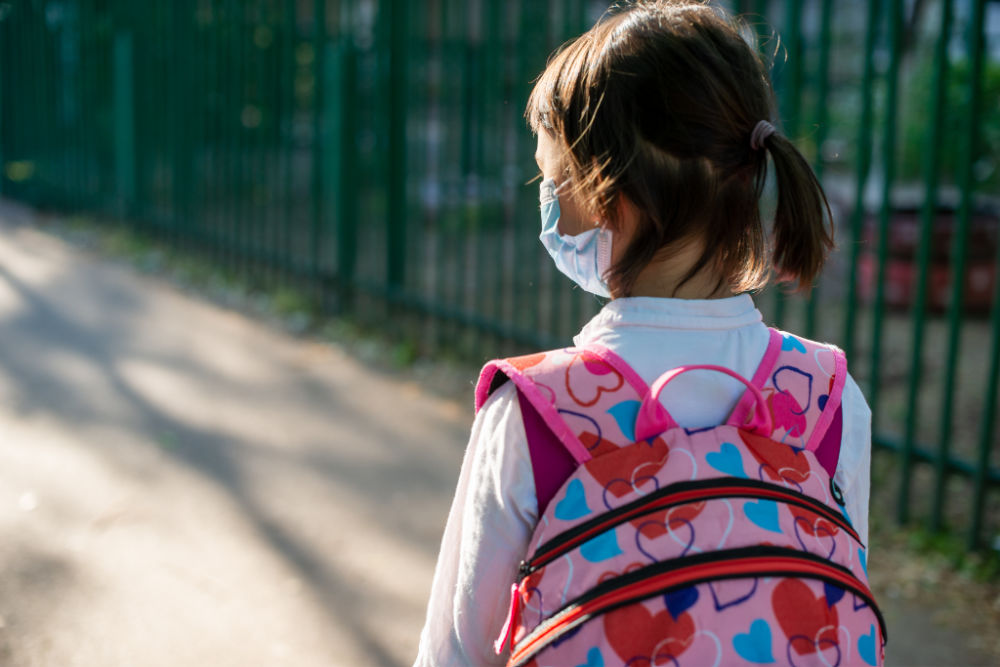 school aged girl with dark brown hair, medical mask, and backpack