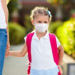 Back to school during a pandemic will mean living in a new normal. Find out how to navigate and balance crisis schooling based on educational psychology. Child in protective mask going back to school